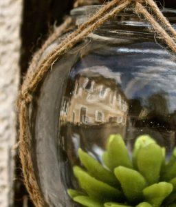 Reflet du Coq en pâte dans un élément de décoration extérieure.